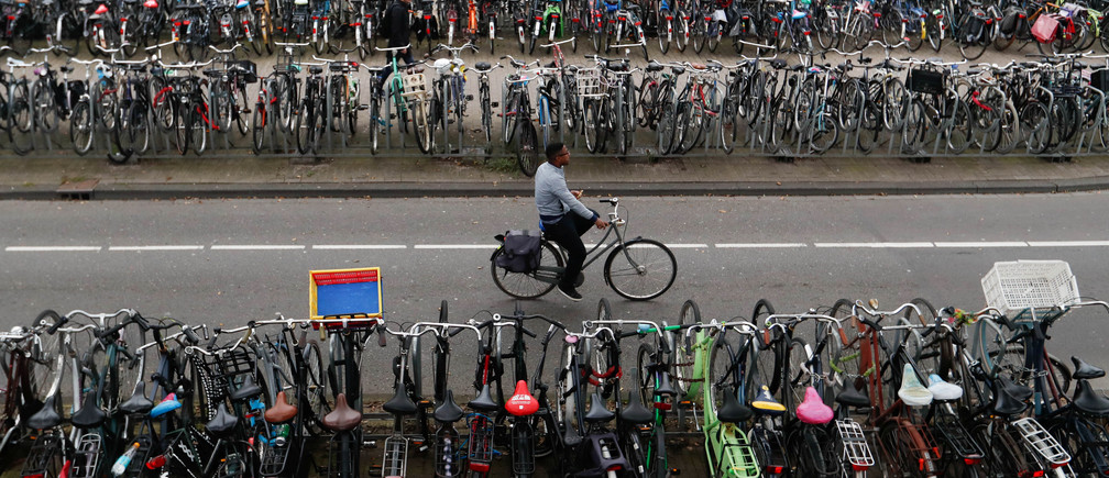 A cyclist rides past a bike parking near Amsterdam Central Station in Amsterdam, Netherlands September 26, 2017. REUTERS/Yves Herman - RC171333C870