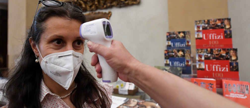 A member of the media wearing a protective mask has her temperature checked as she attends a preview for the media during the reopening of the Uffizi Gallery with new social distancing and hygiene rules in place after months of closure due to the outbreak of the coronavirus disease (COVID-19), in Florence, Italy, June 2, 2020. REUTERS/Jennifer Lorenzini - RC211H90PJPZ