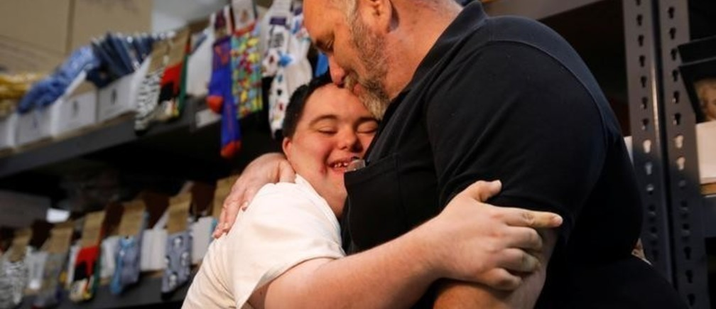 John Cronin, who has Down Syndrome and is co-founder of John's Crazy Socks, embraces his father Mark at John's Crazy Socks, an online sock store that donates a percentage of its sales to charities that help others with disabilities, at the company's headquarters in Melville, New York, U.S., July 23, 2018.  REUTERS/Shannon Stapleton