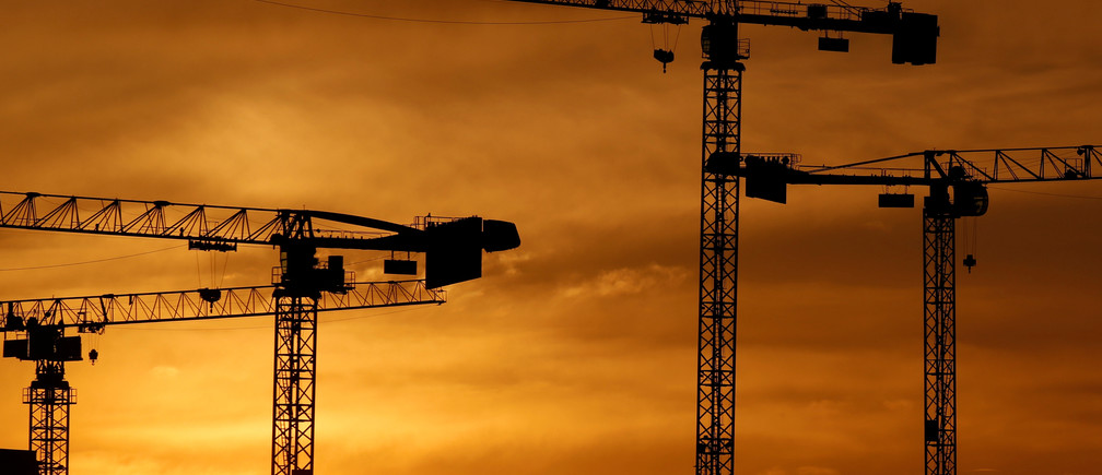 Cranes are seen at sunset at a construction site in Bordeaux, France, April 9, 2019. REUTERS/Regis Duvignau - RC1F4FB022A0