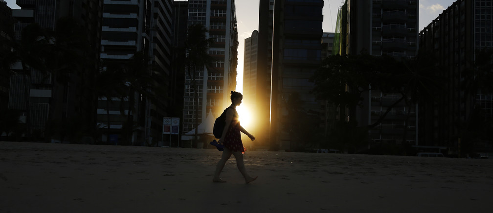 A woman walks on the beach as the sun sets between buildings in Recife June 10, 2014.  In a project called 'OnThe Sidelines' Reuters photographers share pictures showing their own quirky and creative view of the 2014 World Cup in Brazil.  REUTERS/Brian Snyder    (BRAZIL) - RTR3T4DN