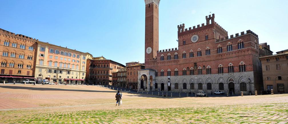 On peut voir de l'herbe sur la Piazza del Campo, qui accueille deux fois par an la course de chevaux du Palio di Siena, qui n'a fait que croître depuis qu'une fermeture stricte a fait que des foules de touristes et d'Italiens ne peuvent plus visiter la place, car la propagation de la maladie à coronavirus (COVID-19) continue, dans la ville médiévale de Sienne, en Italie, le 9 avril 2020.