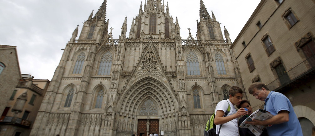 A family looks at a map in front of Barcelona's cathedral at Gothic quarter in Barcelona, Spain, August 18, 2015.