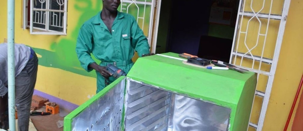 Lawrence Okettayot and Morris Opiyo work on a 'sparky' food dryer at their workshop in Kampala, Uganda, May 13, 2019. Thomson Reuters Foundation/John Okot