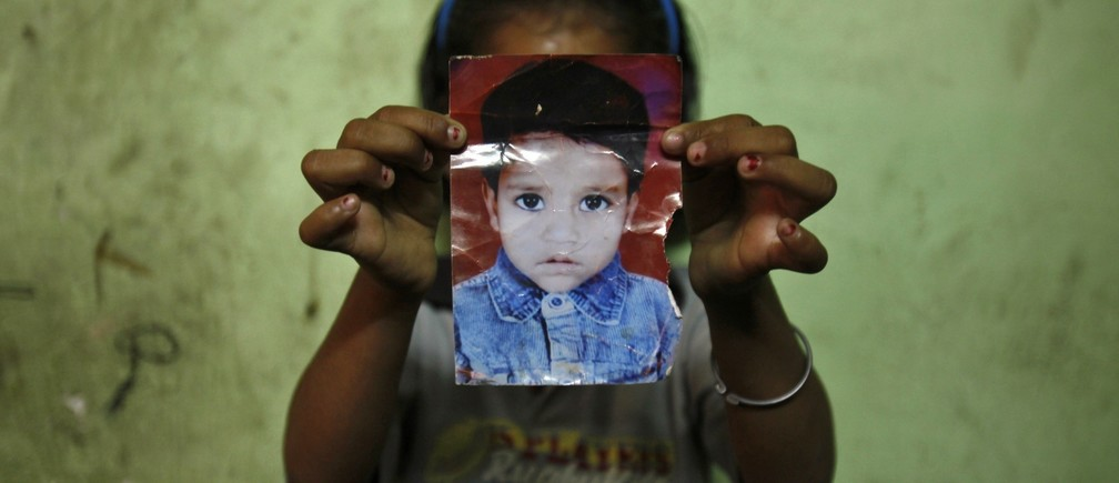 Mansi, 7, poses with a photograph of her missing three-year-old sister Muskaan inside their house in New Delhi April 28, 2013. Muskaan went missing while playing in the neighbourhood on October 30, 2010, according to her family. Between January 1 and May 8, 2013, 725 children in Delhi were reported missing and are untraced, according to data from India's Zonal Integrated Police Network website. Picture taken April 28, 2013. REUTERS/Mansi Thapliyal (INDIA - Tags: SOCIETY CRIME LAW TPX IMAGES OF THE DAY) ATTENTION EDITORS: PICTURE 17 of 17 FOR PACKAGE 'INDIA'S MISSING CHILDREN' SEARCH 'DELHI CHILDREN' FOR ALL - LM2E958130E01