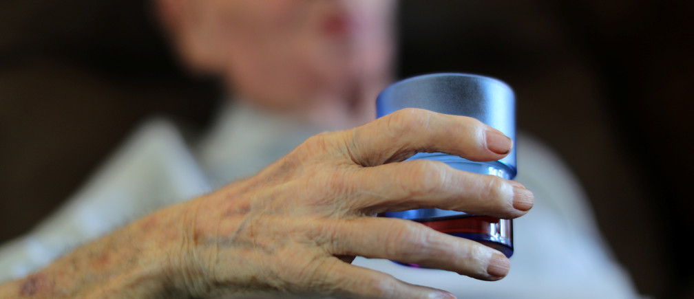 An elderly man holds a glass of syrup during the afternoon break at an elderly home as summer temperatures continue to rise in Nice, France, July 20, 2017.           REUTERS/Eric Gaillard - RC1F304BFD10