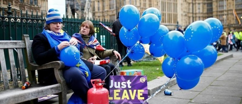 An Anti-Brexit demonstrator sits next to a Pro-Brexit demonstrator outside the Houses of Parliament, in Westminster, London, Britain January 29, 2019. REUTERS/Henry Nicholls     TPX IMAGES OF THE DAY - RC13797105E0