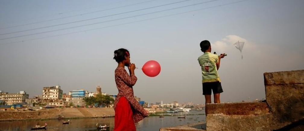 Children enjoy their leisure time with a kite and balloon on the bank of the river Buriganga in Dhaka, Bangladesh, March 12, 2017.