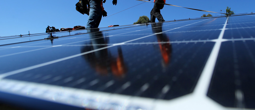 Solar installers from Baker Electric place solar panels on the roof of a residential home in Scripps Ranch, San Diego, California, U.S. October 14, 2016. Picture taken October 14, 2016.       REUTERS/Mike Blake - S1AEUJDNLTAA
