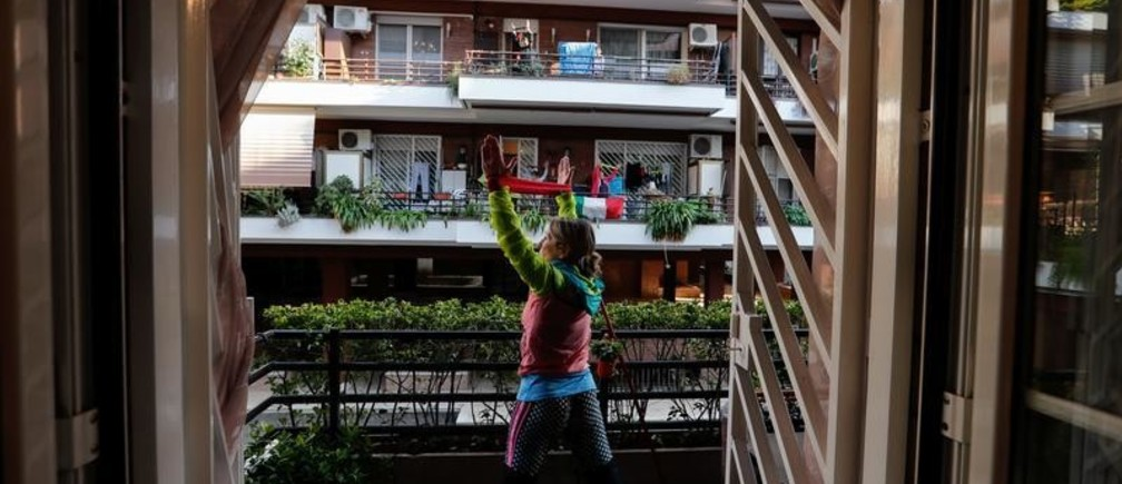 Personal trainer Antonietta Orsini carries out an exercise class for her neighbours from her balcony while Italians cannot leave their homes due to the coronavirus disease (COVID-19) outbreak, in Rome, Italy, March 18, 2020. Picture taken March 18, 2020 REUTERS/Remo Casilli - RC2WMF91LEH7