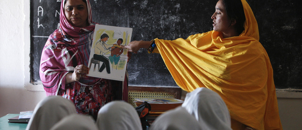 Teachers display a card with an illustration depicting a girl going through a medical checkup by a doctor, as they describe preventive measures to avoid when sexual harassment occurs, during a class in Shadabad Girls Elementary School in Pir Mashaikh village in Johi, some 325 km (202 miles) from Karachi February 12, 2014. Sex education is common in Western schools but these ground-breaking lessons are taking place in deeply conservative rural Pakistan, a Muslim nation of 180 million people. Picture taken February 12, 2014.   REUTERS/Akhtar Soomro (PAKISTAN - Tags: EDUCATION) - GM1EA2P0R8D01