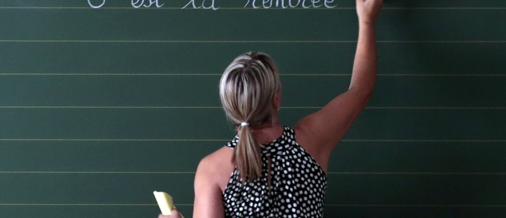 """A teacher writes the phrase """"Today it is the start of the new school year"""" on the blackboard of her classroom on the first day of the new school year at a primary school in Nice, September 3, 2013.    REUTERS/Eric Gaillard (FRANCE - Tags: EDUCATION) - RTX135OQ"""