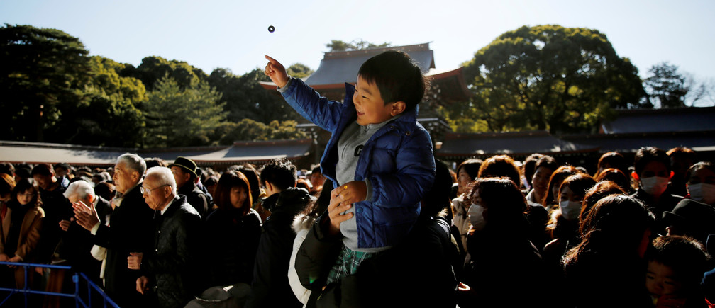 A boy throws a coin as she offers prayers on the first day of the new year at the Meiji Shrine in Tokyo, Japan, January 1, 2019.   REUTERS/Kim Kyung-Hoon - RC18757681F0