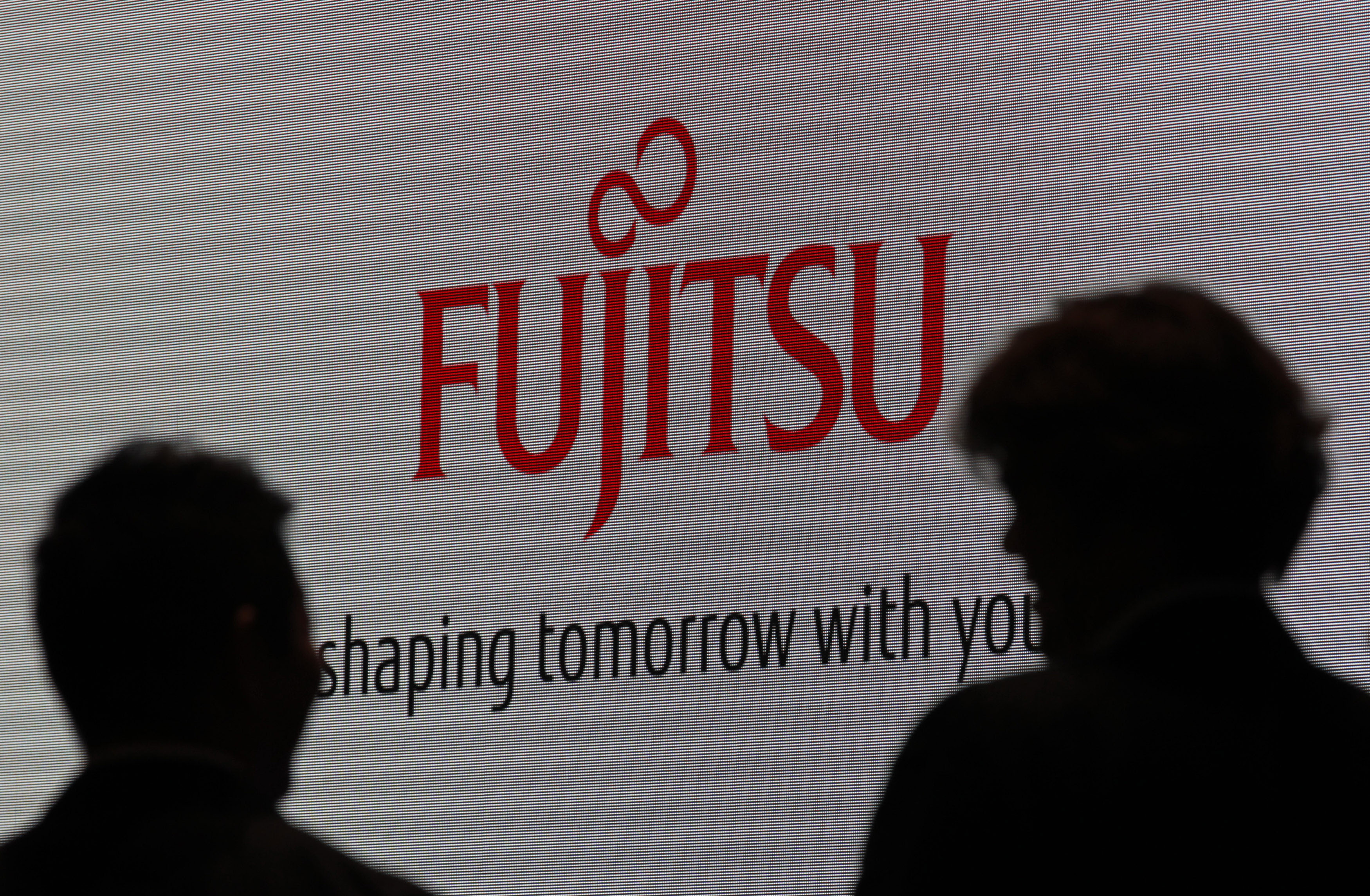 People are silhouetted against a screen displaying a logo of Fujitsu at CEATEC JAPAN 2012 electronics show in Chiba, east of Tokyo, October 2, 2012. Japan's largest cutting-edge IT and electronics trade show started on Tuesday and runs until October 6 at Makuhari Messe convention center. REUTERS/Yuriko Nakao (JAPAN - Tags: BUSINESS) - GM1E8A21I2401