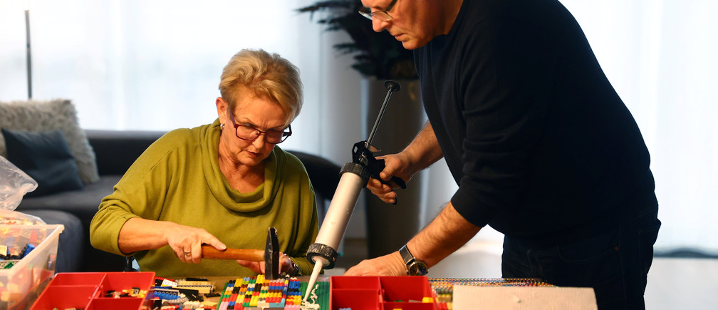 """Rita Ebel (L), nicknamed """"Lego grandma"""", and her husband Wolfgang build a wheelchair ramp from donated Lego bricks in the living room of their flat in Hanau, Germany, February 17, 2020. Picture taken February 17, 2020. Ebel started to build the ramps almost one year ago to raise awareness for handicapped people in her hometown of Hanau. Meanwhile, dozens of stores use the ramps to ease entry for wheelchair users.  REUTERS/Kai Pfaffenbach - RC2X2F9FM86I"""