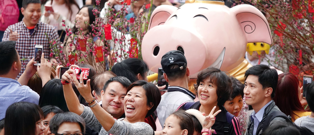 Visitors take pictures of an installation at a flower fair ahead of the Chinese Lunar New Year of the Pig, in Guangzhou, Guangdong province, China February 3, 2019. Picture taken February 3, 2019.  REUTERS/Stringer ATTENTION EDITORS - THIS IMAGE WAS PROVIDED BY A THIRD PARTY. CHINA OUT. - RC137BD315B0