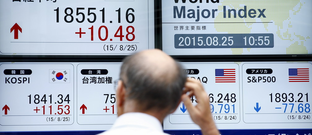 A man looks at screens displaying market indices at a brokerage in Tokyo, August 25, 2015. Asian stocks looked vulnerable to another sell-off on Tuesday, with investors gripped by fears of a hard landing for the Chinese economy, the world's most important growth engine.  REUTERS/Thomas Peter - GF10000181743