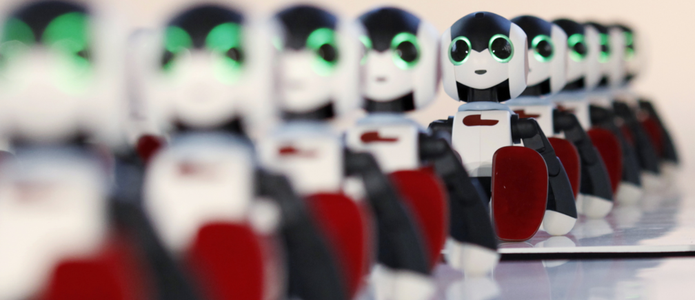 A hundred humanoid communication robots called Robi sit before a dance performance dance during a promotional event called 100 Robi, for the Weekly Robi Magazine, in Tokyo January 20, 2015.  The 34cm-tall (13.4-inch) robot, designed by Tomotaka Takahashi, chief executive officer of Robo Garage Co and project associate professor of Research Centre for Advanced Science and Technology at the University of Tokyo, is able to speak, walk and dance. The weekly magazine comes with parts of the robot, which allows buyers to have a fully assembled Robi after 70 issues. REUTERS/Yuya Shino (JAPAN - Tags: SOCIETY BUSINESS)