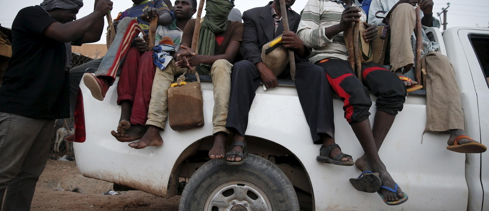 Migrants sit in the back of a truck at a local immigration transit centre in the desert town of Agadez, Niger May 25, 2015. African migrants in overcrowded pickup trucks, encouraged by social media messages from friends who survived the perilous journey across the Mediterranean, set off from Agadez, an ancient trading town on the edge of the Sahara, to cross Niger in the uncertain journey towards Europe via Libya, where the collapse of the government has offered an open door for smugglers. Mostly young men, escaping grinding poverty in neighbouring Benin or Burkina Faso, face bandits and often have to pay bribes en route, on top of the hefty payments to people smugglers. International focus on the issue of migration into Europe has sharpened after hundreds of migrants drowned while trying to cross the sea from North Africa in overcrowded and unsafe vessels.   REUTERS/Akintunde Akinleye    TPX IMAGES OF THE DAY PICTURE 34 OF 36 FOR WIDER IMAGE STORY 'SMUGGLED THROUGH NIGER'SEARCH 'SAHARA AKINLEYE' FOR ALL IMAGES      TPX IMAGES OF THE DAY      - RTX1EXBV