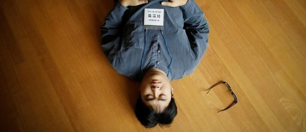 """A participant meditates before being locked up in a cell at Prison Inside Me, a mock prison facility, in Hongcheon, South Korea, November 10, 2018. Since 2013, the facility has hosted more than 2,000 inmates, many of them stressed office workers and students seeking relief from South Korea's demanding work and academic culture. REUTERS/Kim Hong-Ji       SEARCH """"PRISON RETREAT"""" FOR THIS STORY. SEARCH """"WIDER IMAGE"""" FOR ALL STORIES. - RC16B04AA360"""
