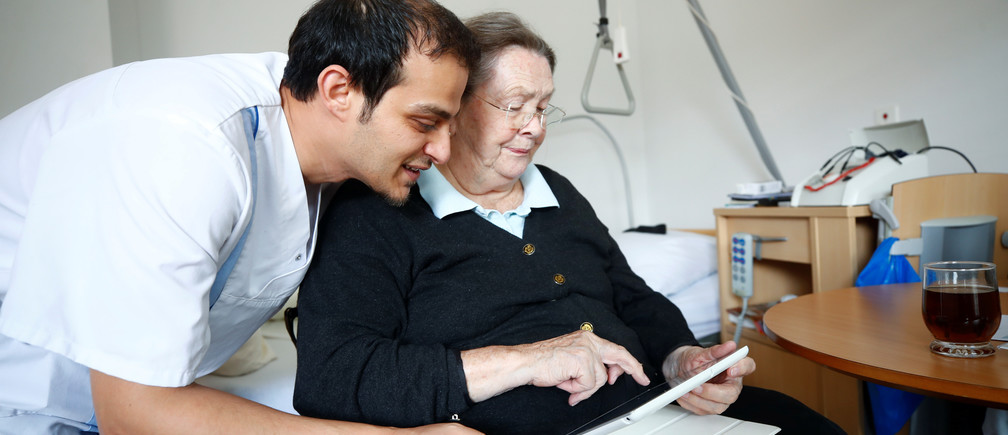 "Elisabeth Grohmann, an 85-year-old former sports teacher and Amer Kabara, a 35-year-old former refugee from Syria watch a funny movie about Germany's anti-refugee party Alternative fuer Deutchland AFD on Grohmann's tablet at an old people's home in Duesseldorf, Germany, September 12, 2018. Picture taken September 12, 2018. Kabara, who fled to Germany from the civil war-torn Syrian capital of Damascus is on an 18-month educational project called ""Care for Integration"" to become a state-approved nurse for the elderly in Germany.  REUTERS/Wolfgang Rattay - RC1D5ED12810"