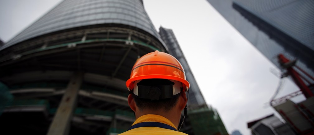 A construction worker stand at the base of the Shanghai Tower (L), which is under construction, at the financial district of Pudong in Shanghai August 2, 2013.