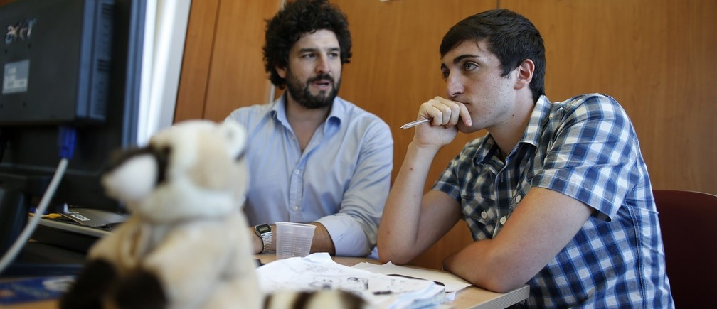 Matteo Achilli (R) works with one of his assistants in his office in Formello, north of Rome July 25, 2013. Achilli, dubbed the Italian Zuckerberg by Panorama Economy, is the 21-year-old founder of Egomnia, a social network created to match companies looking to hire graduate job seekers. According to Achilli, Egomnia, which was founded in February 2012, has around 100,000 users, about 600 multinational companies in Italy as clients and a 2013 sales volume of about 500,000 euros. Picture taken July 25, 2013.REUTERS/Tony Gentile (ITALY - Tags: BUSINESS EMPLOYMENT) - RTX1201Y