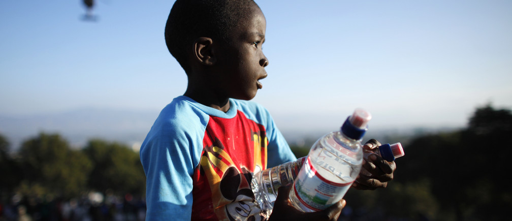 A Haitian boy receives water from U.S. forces at a food distribution point in Port-au-Prince January 19, 2010. Thousands more U.S. troops will help U.N. peace keepers keep order on Haiti's increasingly lawless streets as tens of thousands of survivors wait desperately for aid.  REUTERS/Jorge Silva (HAITI - Tags: DISASTER ENVIRONMENT IMAGES OF THE DAY) - GM1E61K03ZQ01