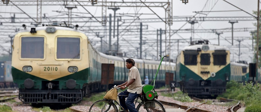A man rides his bicycle across the railway tracks at Ghaziabad train station in the outskirts of Delhi, India, June 28, 2017. REUTERS/Cathal McNaughton - RC1CA64A5400