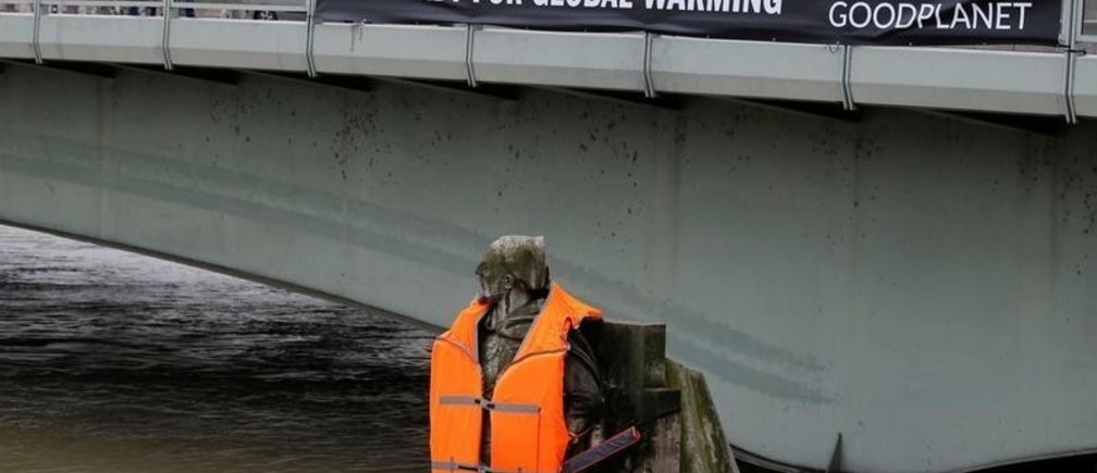 """A banner hangs from the Pont d'Alma bridge with the message, """"Get Ready for Global Warming"""", above the Zouave soldier statue that wears a life vest as high waters from rain continue to cause the Seine River to overflow its banks, in Paris, France, February 4, 2018. REUTERS/Regis Duvignau - RC1534CA56F0"""