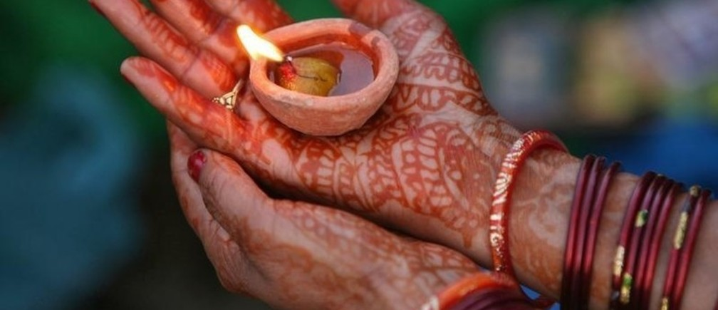 "A Hindu woman devotee with her hands decorated with henna paste holds an earthen oil lamp while worshipping the Sun god during the Hindu religious festival ""Chhat Puja"" in Jammu November 1, 2011. Hindu devotees worship the Sun god and fast all day for the betterment of their family and society during the festival."
