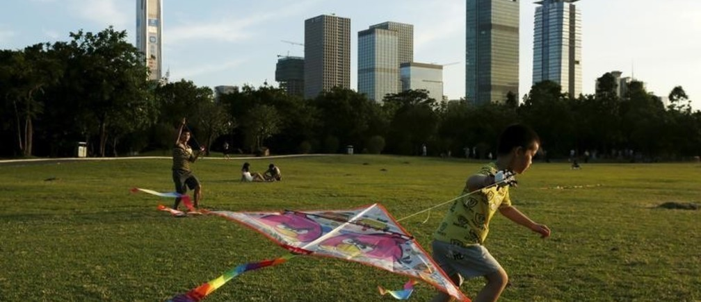 People fly kites at a park in front of commercial towers, including the 115-storey Ping An International Finance Centre (L), which is under construction, in Shenzhen, China August 3, 2015. A stream of weak manufacturing data, the fall in the yuan and a stock market rout have painted a gloomy picture of the world's second largest economy over the past few months. But for the property market in China's boomtown of Shenzhen, thing's couldn't be better. Real estate prices in China's answer to Silicon Valley rose by almost a third in August from the same month a year-ago, a further climb from the nearly 24 percent year-on-year increase in July, official data showed, making it the country's hottest property market by far. Picture taken August 3, 2015.  REUTERS/Bobby Yip - GF10000232700