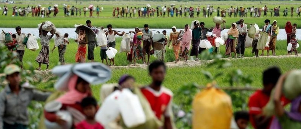 """Rohingya refugees, who crossed the border from Myanmar two days before, walk after they received permission from the Bangladeshi army to continue on to the refugee camps, in Palang Khali, near Cox's Bazar, Bangladesh October 19, 2017. Reuters photographer Jorge Silva: """"This picture was taken after a huge group of people crossed into Bangladesh and then had to wait three days and nights for the Bangladeshi Army's permission to continue walking into the makeshift camps. The line of people seemed endless. Long hours moving slowly across the embankments of the rice field. Mothers with babies and pregnant women, elderly people with illnesses, men carrying their entire life on their shoulders. They were safe from violence, but the challenge of surviving was still waiting for them on this side of the river."""" REUTERS/Jorge Silva/File Photo   SEARCH """"POY ROHINGYA"""" FOR THIS STORY. SEARCH """"REUTERS POY"""" FOR ALL BEST OF 2017 PACKAGES.  TPX IMAGES OF THE DAY. - RC1DF361B970"""