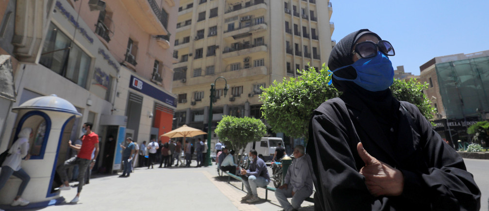 A woman wearing a protective mask looks on as people wait to make withdrawals outside a branch of Commercial International Bank (CIB), amid concerns over the coronavirus disease (COVID-19) in Cairo, Egypt May 31, 2020. Picture taken May 31, 2020. REUTERS/Amr Abdallah Dalsh - RC2D0H95JMAW
