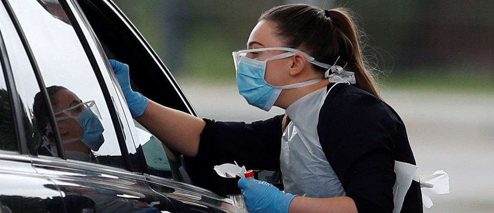 Medical staff at an NHS drive through coronavirus disease (COVID-19) testing facility in the car park of Chessington World of Adventures, as the spread of the coronavirus disease (COVID-19) continues, Chessington, Britain, March 30, 2020. REUTERS/Peter Nicholls - RC2BUF9H9NBI
