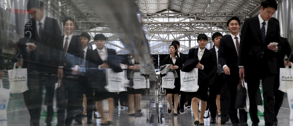 Job seekers walk towards a job fair held for fresh graduates in Tokyo, Japan, March 20, 2016.