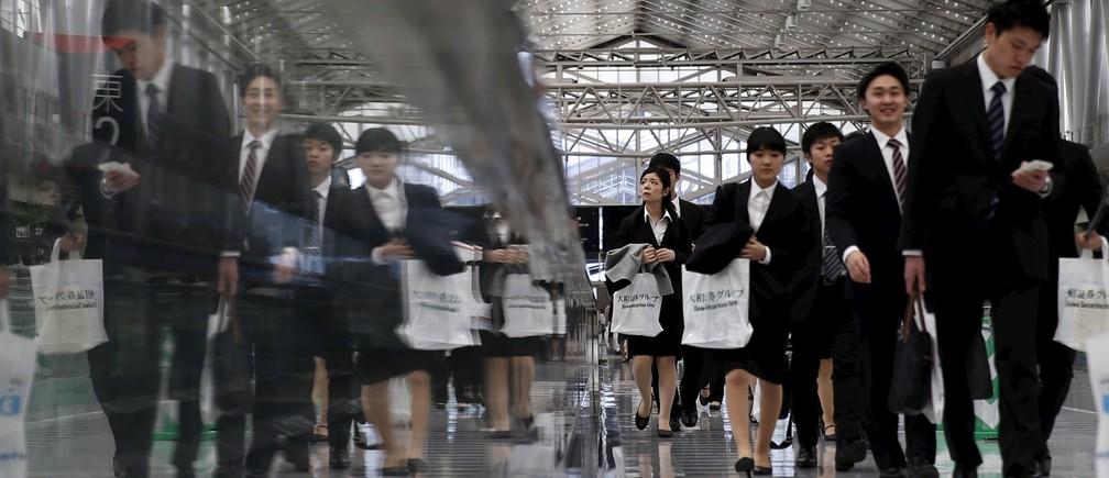 Job seekers walk towards a job fair held for fresh graduates in Tokyo, Japan, March 20, 2016.