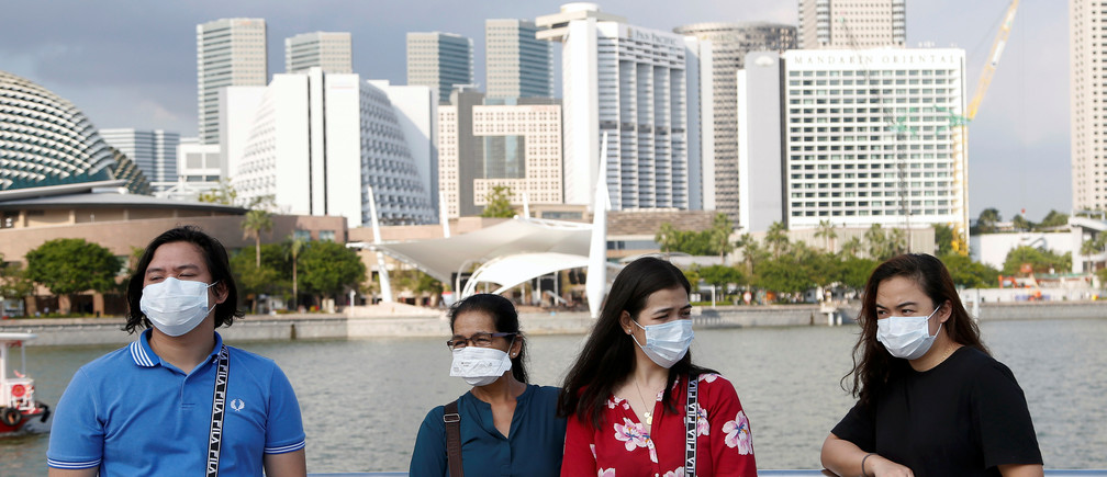 Tourists wear protective face masks at the Merlion Park in Singapore, January 28, 2020. REUTERS/Feline Lim - RC20PE9Y73XW