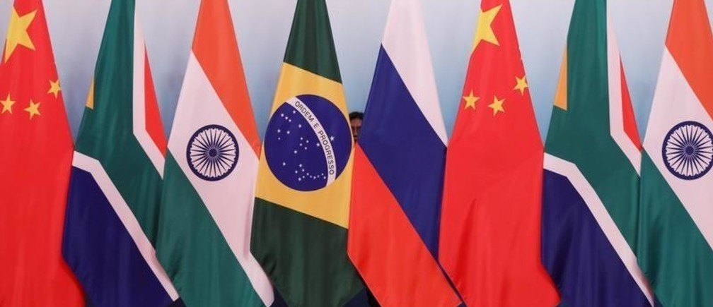 A staff worker stands behind the national flags of Brazil, Russia, China, South Africa and India to tidy the flags before a group photo during the BRICS Summit at the Xiamen International Conference and Exhibition Center in Xiamen, southeastern China's Fujian Province, China September 4, 2017. REUTERS/Wu Hong/Pool - RC1BBBFA1AD0