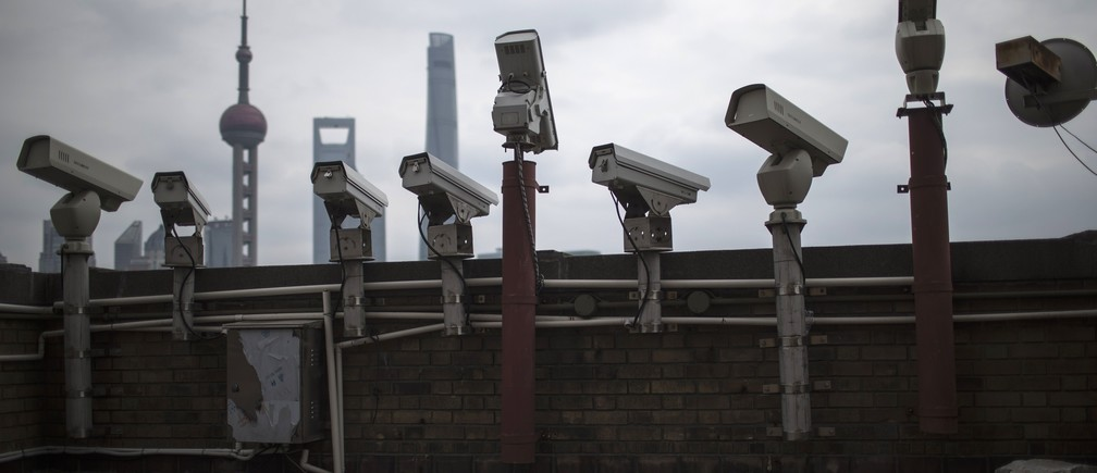 Security cameras are seen on a building at the Bund in front of the financial district of Pudong in Shanghai March 6, 2015.