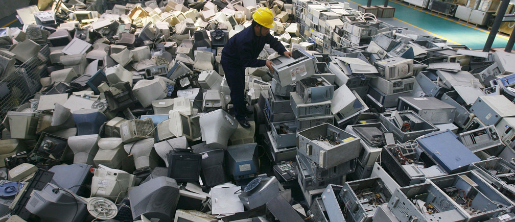 An employee arranges discarded computers at a newly opened electronic waste recycling factory in Wuhan, Hubei province March 29, 2011. According to the U.S. Environmental Protection Agency (EPA), e-waste is the fastest growing commodity in the waste stream, with a growth rate five times that of other parts of the business such as industrial waste. The burgeoning middle classes in fast-growth China and India mean there are more computers and mobiles, adding to e-cycling growth. REUTERS/Stringer (CHINA - Tags: ENVIRONMENT IMAGES OF THE DAY BUSINESS SCI TECH) CHINA OUT. NO COMMERCIAL OR EDITORIAL SALES IN CHINA. BEST QUALITY AVAILABLE - GM1E73T1GS701