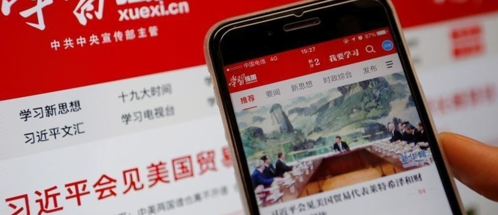 Chinese government propaganda app Xuexi Qiangguo, which literally translates as 'Study to make China strong',  is seen on a mobile phone in front of its website on a computer screen in this illustration picture taken February 18, 2019. REUTERS/Tingshu Wang/Illustration u000d u000d - RC1AD22889B0