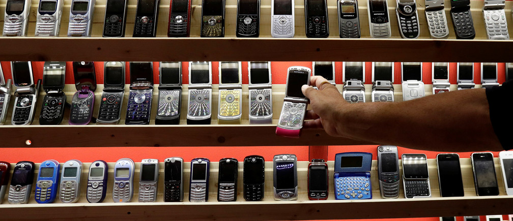 A man grabs an old mobile phone inside of a private museum of phones in Dobsina, Slovakia, September 6, 2017. Picture taken September 6, 2017. REUTERS/David W Cerny