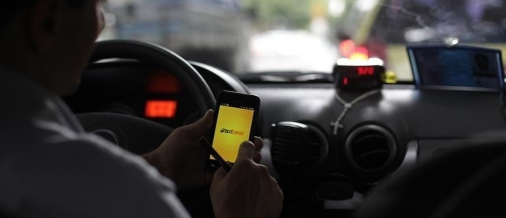 A taxi driver checks an app on his smartphone in Rio de Janeiro April 15, 2013. Picture taken on April 15, 2013.