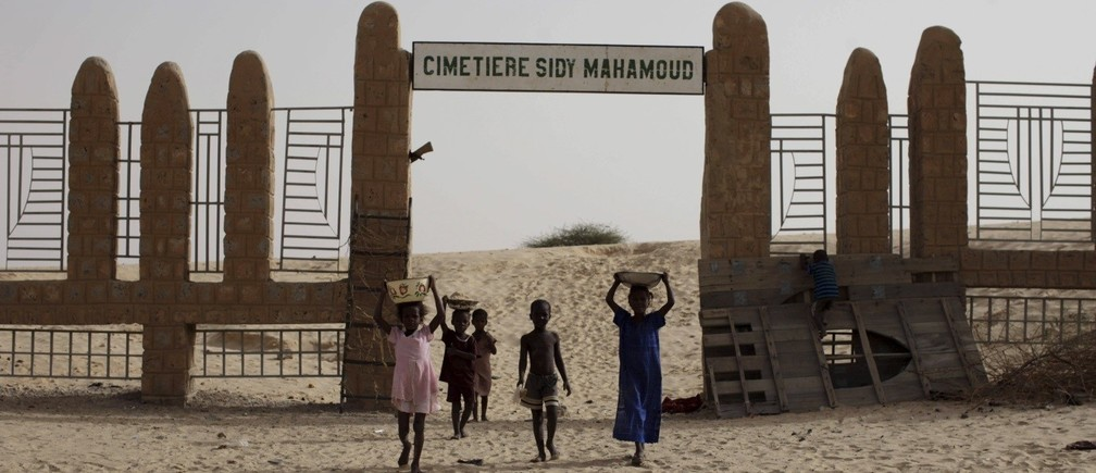 Children walk in front of the Sidy Mahamoud cemetery, where Islamist militants destroyed ancient mausoleums in Timbuktu, Mali, July 25, 2013.