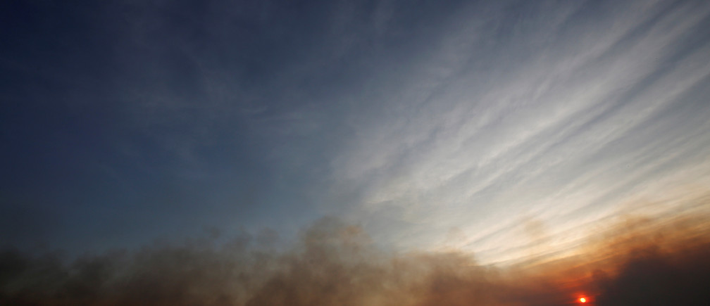 Smoke from a forest fire is seen during sunset in an area of Chapada dos Veadeiros National Park, in Alto Paraiso, Goias, Brazil, October 24, 2017. REUTERS/Ueslei Marcelino - RC18F8C41200