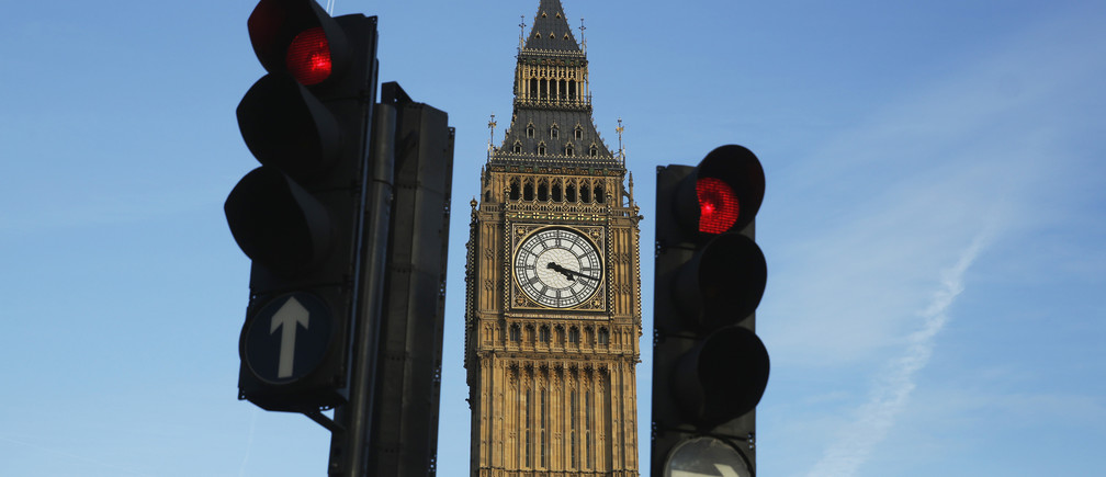 Red traffic lights stop traffic in front of the Big Ben bell tower at the Houses of Parliament in London