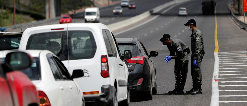 Border policemen chat to a driver at a roadblock set-up by police as they begin to enforce a national lockdown to fight the spread of the coronavirus disease (COVID-19) on a road leading to Jerusalem, near Ein Hemed, Israel April 7, 2020. REUTERS/Ronen Zvulun - RC2MZF9ZZ2OD