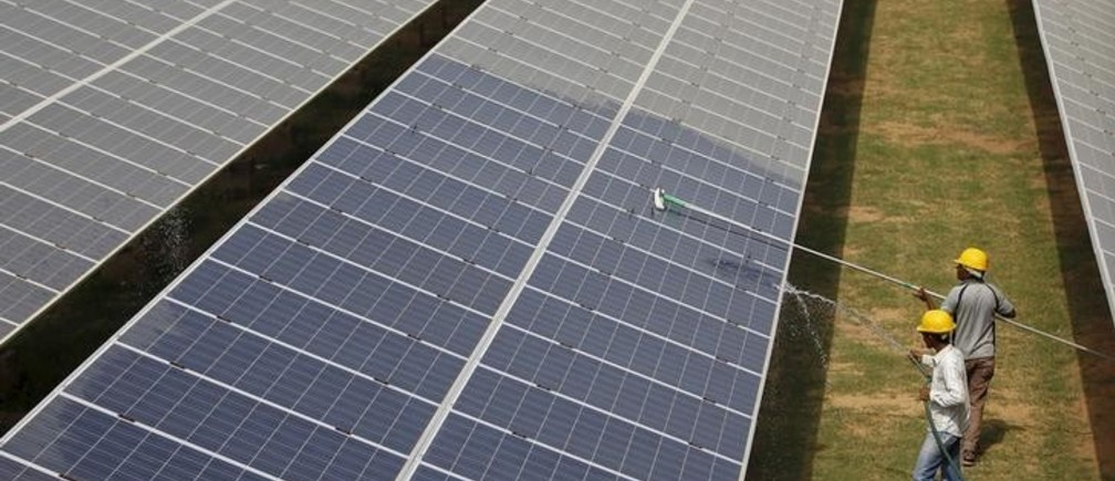 "Workers clean photovoltaic panels inside a solar power plant in Gujarat, India, in this July 2, 2015 file photo. The likely collapse of SunEdison Inc's solar project in India, the first of 32 planned ""ultra mega"" complexes, could delay Prime Minister Narendra Modi's goal to increase renewable energy fivefold by several years and probably cost consumers more. REUTERS/Amit Dave/Files"
