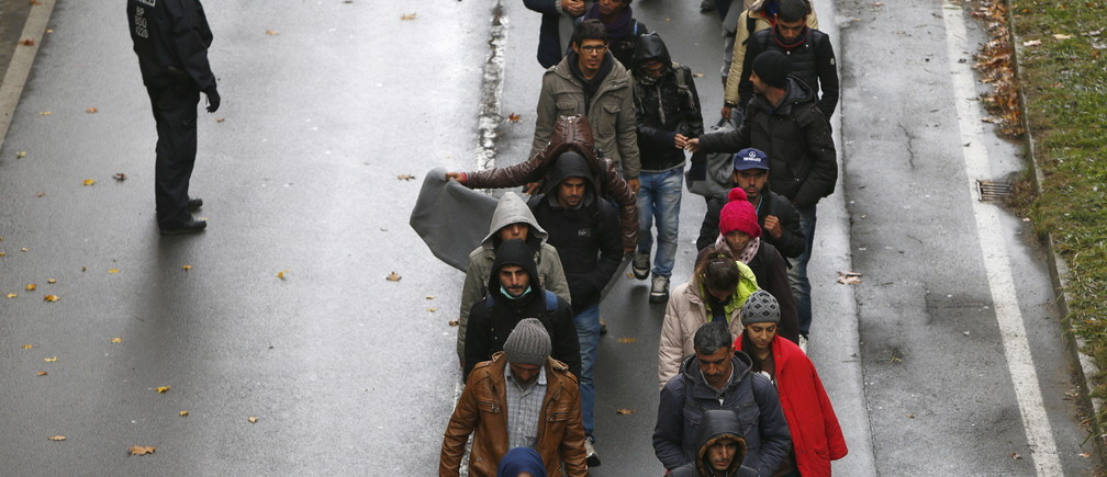 Migrants walk along a street after crossing the Austrian-German border from Achleiten, Austria, in Passau, Germany, October 29, 2015. German Chancellor Angela Merkel came under intense pressure for her handling of the refugee crisis on Wednesday, with her Bavarian allies warning of a full-blown coalition crisis unless she takes immediate action to limit a record influx of migrants.